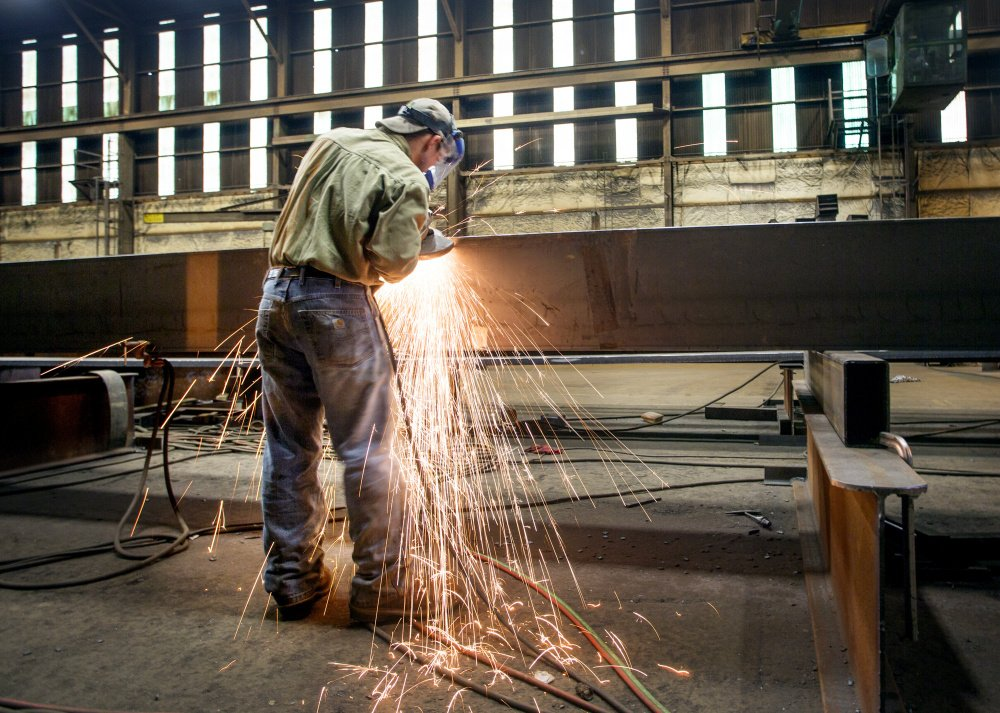 Dustin Ford grinds a steel girder at Casco Bay Steel.
