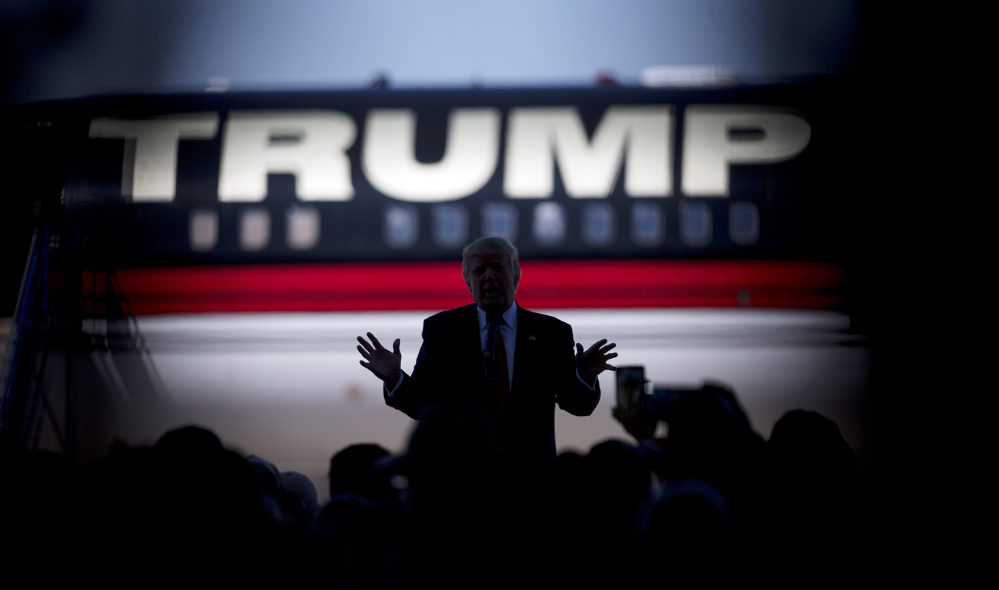 The Associated Press In this Feb. 27, 2016 file photo, Republican presidential candidate Donald Trump is silhouetted against his plane as he speaks during in Bentonville, Ark., as shot through the crowd.