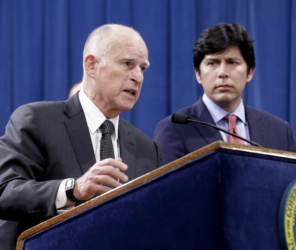 Accompanied by labor leaders and Senate President Pro Tem Kevin de Leon, D-Los Angeles, right, California Gov. Jerry Brown discusses proposed legislation to increase the state's minimum wage to $15 per hour by 2022, during a March 28 news conference in Sacramento.