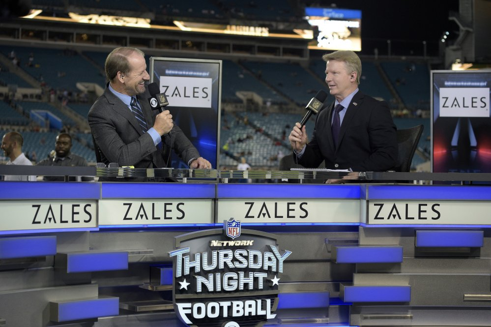 Thursday Night Football sportscasters Bill Cowher, left, and Phil Simms broadcast from the set on the field before an NFL football game between the Jacksonville Jaguars and the Tennessee Titans in Jacksonville, Fla. The NFL has picked Twitter to stream its Thursday night games.