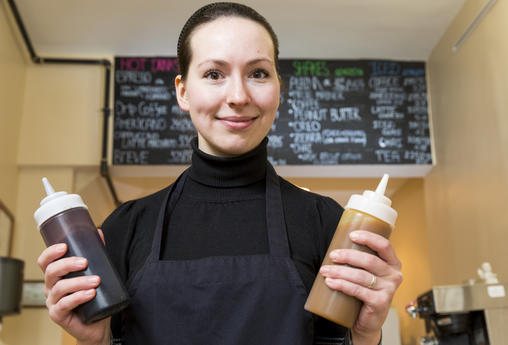 Yulia Stolkner hoists squeeze bottles of chocolate and caramel at her newly opened cafe Sip of Europe at 229 Congress St.