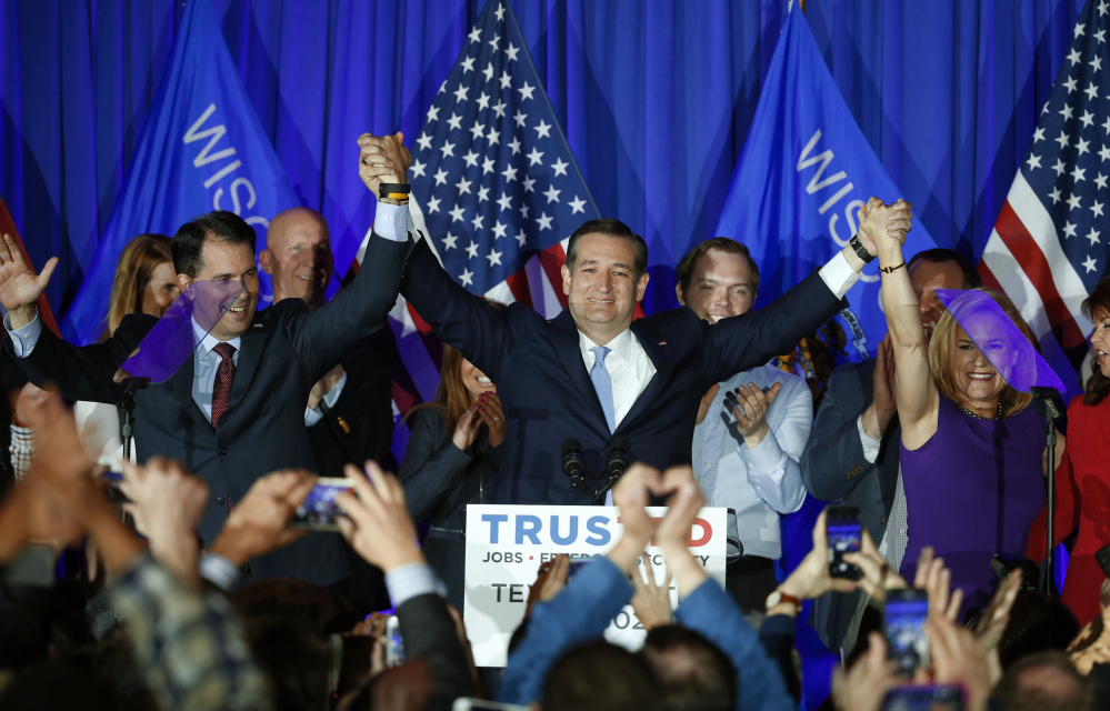 Republican presidential candidate Sen. Ted Cruz, R-Texas, raises hands with Wisconsin Gov. Scott Walker, left, and his wife Heidi, right, during a primary night campaign event Tuesday.