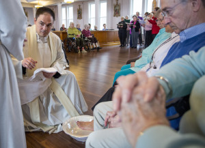 The Rev. Paul Dumais says Mass (above) and the washes the feet of worshippers (below) on Holy Thursday at the d'Youville Pavillion at St. Mary's Hospital in Lewiston.