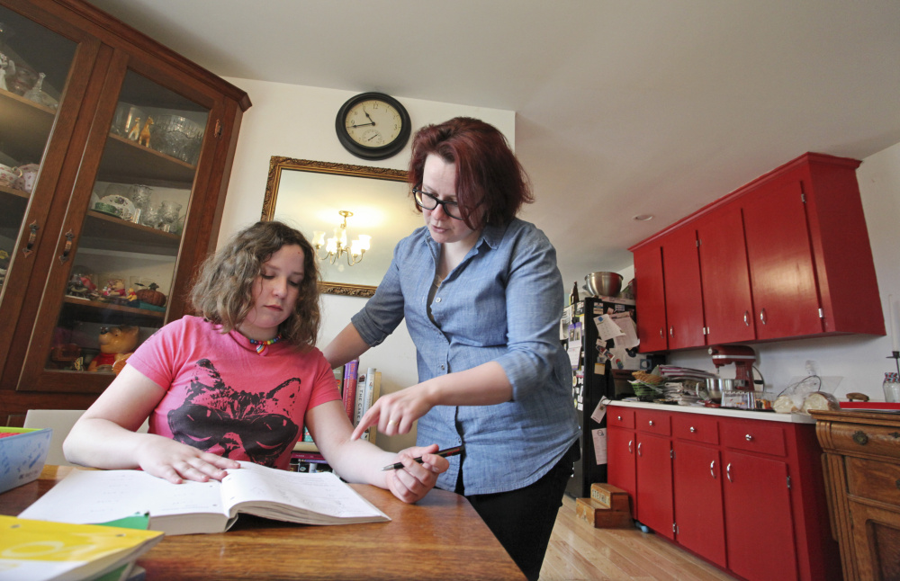 Homeschooling parent Lea Verrill helps daughter Clara with her math in North Yarmouth. Maine law doesn't do much to ensure that all homeschooled children get the well-rounded education they're entitled to.