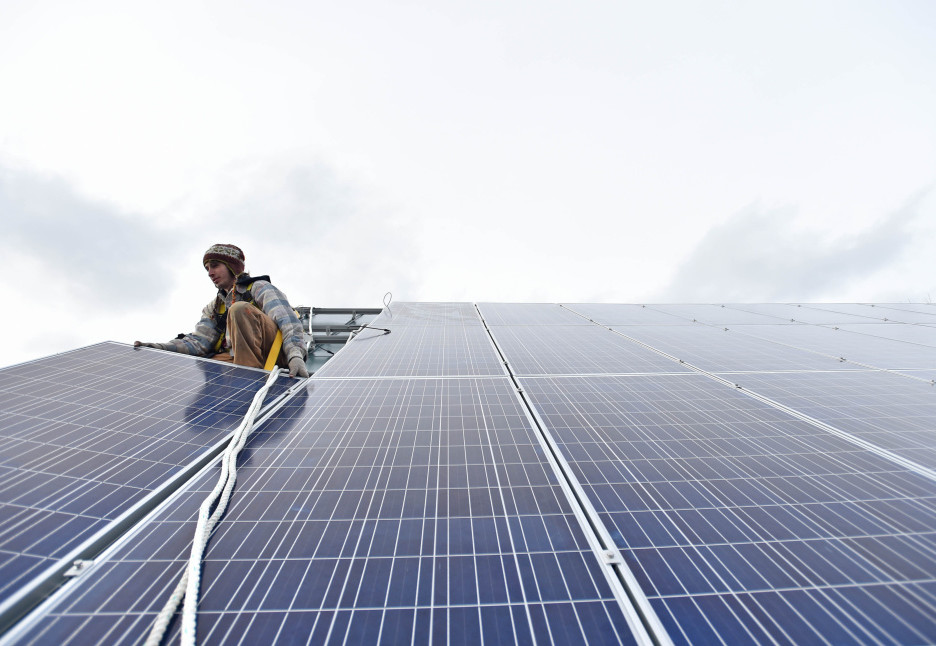 Insource Renewables employee Ben Holt installs a solar panel on the Vassalboro Friends Meeting House in East Vassalboro. The 23-year-old worries he may have to go out of state to find work in the renewable energy field if the state Legislature can't muster support for net metering.  (Michael G. Seamans/Morning Sentinel)