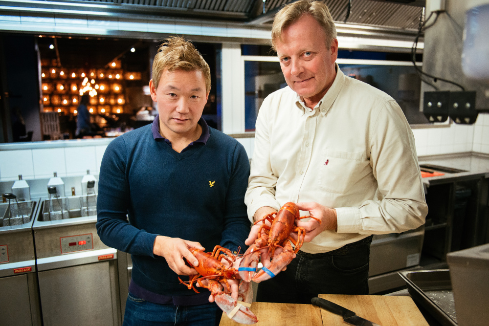 "Thomas Dahlstedt, left, who co-owns and manages Stockholm's Burger & Lobster, and Chef Anders Westerholm hold cooked North American lobsters. A proposed import ban is ""too dramatic,"" Westerholm said."