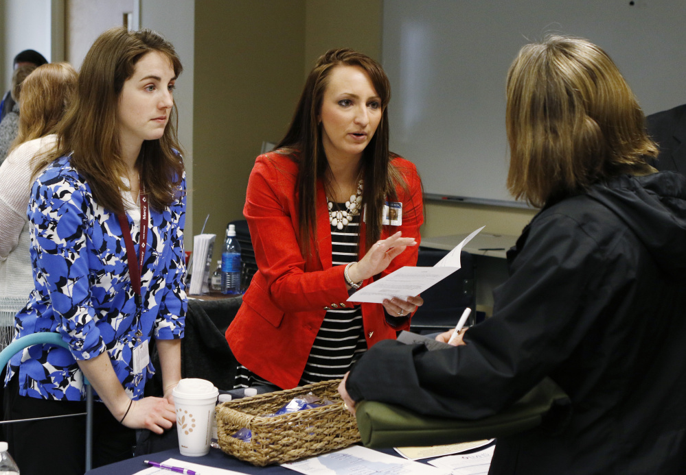 Elizabeth Keenan, center, and Brittany Tyner, left, of Eastern Maine Health Services, distribute employment information to former Merrymeeting employees.