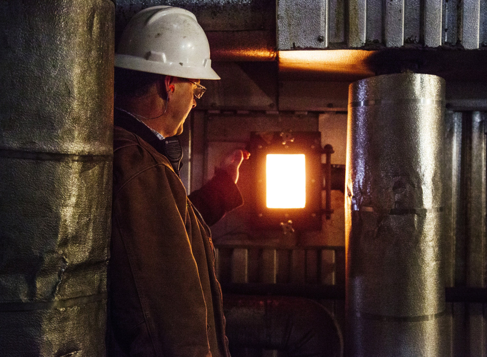 David Ettinger of ReEnergy opens a window into the biomass plant in Livermore Falls. The future of one or two of the company's four biomass plants in Maine is at risk.