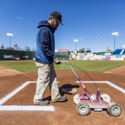 Jason Cooke, the assistant groundskeeper at Hadlock Field, paints the batters' boxes in preparation for Thursday night's home opener.
