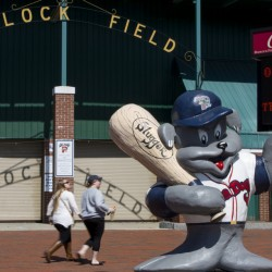A sign held by Slugger announces opening day at Hadlock Field, which now has metal detectors. State law prohibits firearms in venues that hold liquor licenses.