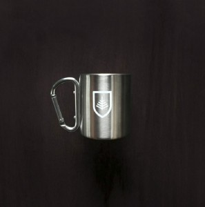 Products developed by Might & Main include, from left, an insulated mug with a carabiner handle; a baseball cap with a Dirigo patch; and enamel mugs.