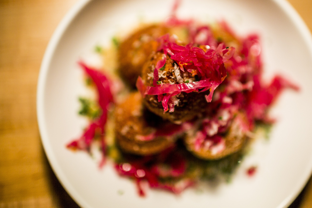 The arancini rest on eggplant puree and are topped with pickled cabbage.