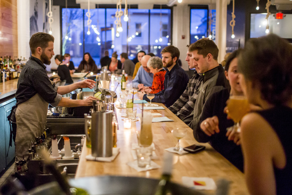 Kit Paschal, co-owner of Roustabout, mixes a drink while chatting with patrons during dinner service.