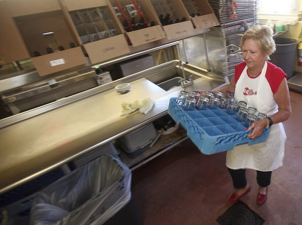 Lobster Claw Restaurant co-owner Marylou Berig, 73, puts away clean glasses after washing them in the morning before the restaurant opens. The Berigs, like many of Cape Cod's seasonal business owners, are dealing with the fallout from a federal government delay in processing H-2B visas for seasonal non-immigrant workers.
