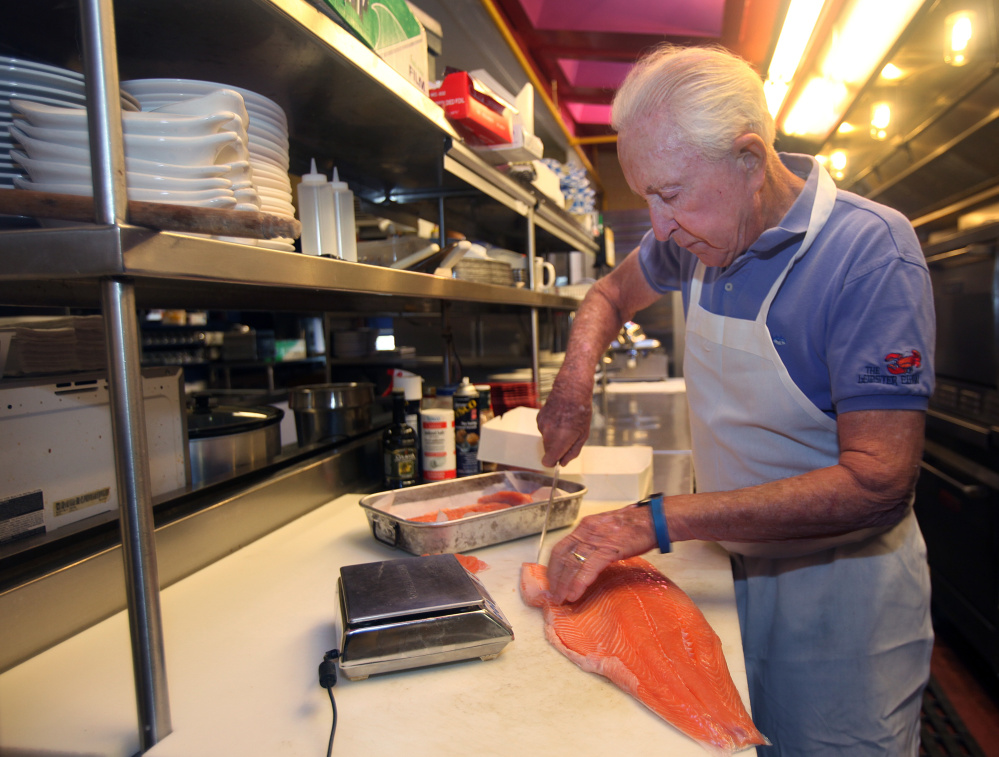Lobster Claw Restaurant co-owner Don Berig, 76, cuts up some salmon to prepare for the 11:30 a.m. opening. Putting in 15-hour days as cook and cleaner is not what he expected to be doing at this point in his life, but he and his wife, Marylou, are on the front lines at the Lobster Claw until the restaurant's seasonal workforce arrives.