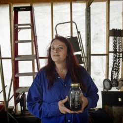 """Michelle Ham, 37, of Shapleigh, holds a jar of medical marijuana tincture mixed with glycerin. To medicate chronic pain, Ham used to take a daily combination of 29 prescription pills, including opiates, but has made the switch to cannabis. """"I have my life back now,"""" she says."""