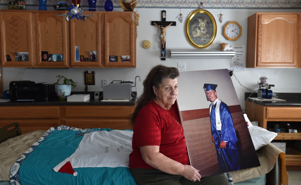 Angela Hinck last week sits on her son Aaron Mullen's bed with a graduation picture of him from 1994. Mullen was shot in the head months after graduating from high school. He lived in a coma for more than 21 years until he died on April 9.