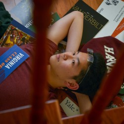 Apollo Yong, 17, reclines on a bed of college paraphernalia at home in Arlington, Va. A strong candidate, he nevertheless is among thousands placed on college wait lists.