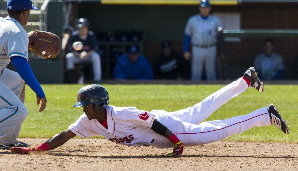 Jose Vinicio of the Sea Dogs dives safely back to first base on a pickoff attempt Sunday as Hartford Yard Goats first baseman Correlle Prime fields the throw. The Sea Dogs lost, 8-1.
