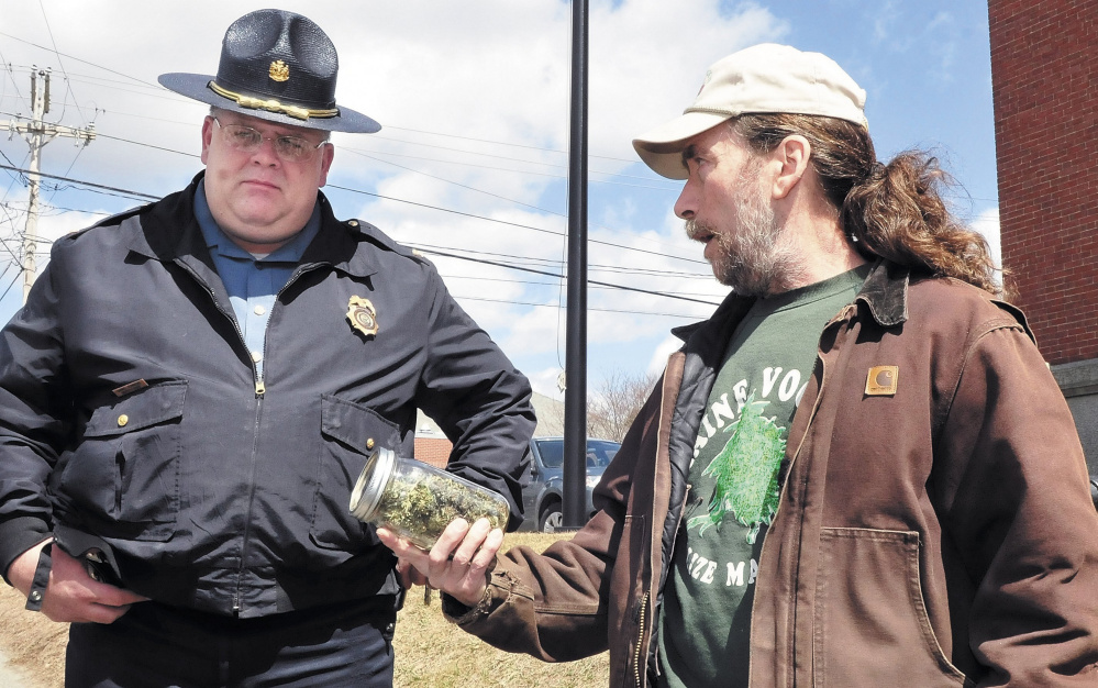 Marijuana legalization advocate Donny Christen shows a jar of marijuana to Skowhegan Deputy Police Chief Dan Summers during the Patriot's Day smoke-in on the steps of the Somerset County Courthouse in 2013. The annual smoke-in is his continued effort to draw attention to legalize marijuana. Christen is a medical marijuana patient and can legally possess the drug.
