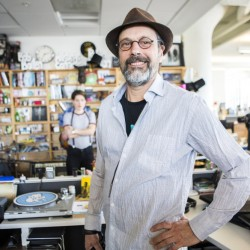 "Bob Boilen, host of the ""Tiny Desk Concerts"" series, pauses during a sound check for the artist Monika at his NPR desk in Washington."
