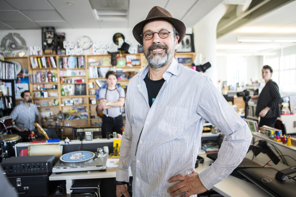 """Bob Boilen, host of the """"Tiny Desk Concerts"""" series, pauses during a sound check for the artist Monika at his NPR desk in Washington."""