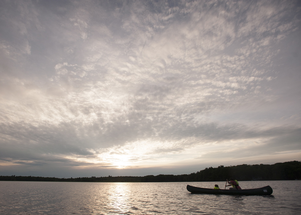 Ruth Bagless of Bangor and her daughter, Frances, paddle across the water on Fields Pond to explore birds and nature as part of the Maine Audubon's evening paddle. Fields Pond is one of the eight Audubon centers in the state.