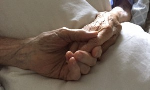 At left, Robert and Lucille Robinson hold hands Monday in their beds at a Falmouth assisted living facility.