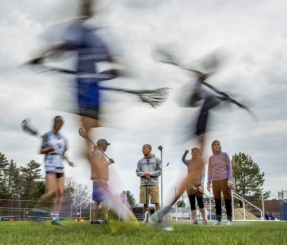 Joe Schwartzman, center, the athletic director in Kennebunk schools, confers with volunteer assistant coach Joe Bush, center left, as they lead the junior varsity girls' lacrosse practice Friday. Schwartzman stepped into the coach's position this spring after he got no applicants for the job.