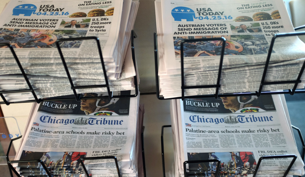 USA Today, Chicago Tribune and other newspapers are displayed at Chicago's O'Hare International Airport. Gannett is trying to buy Tribune Publishing for more than $388 million.