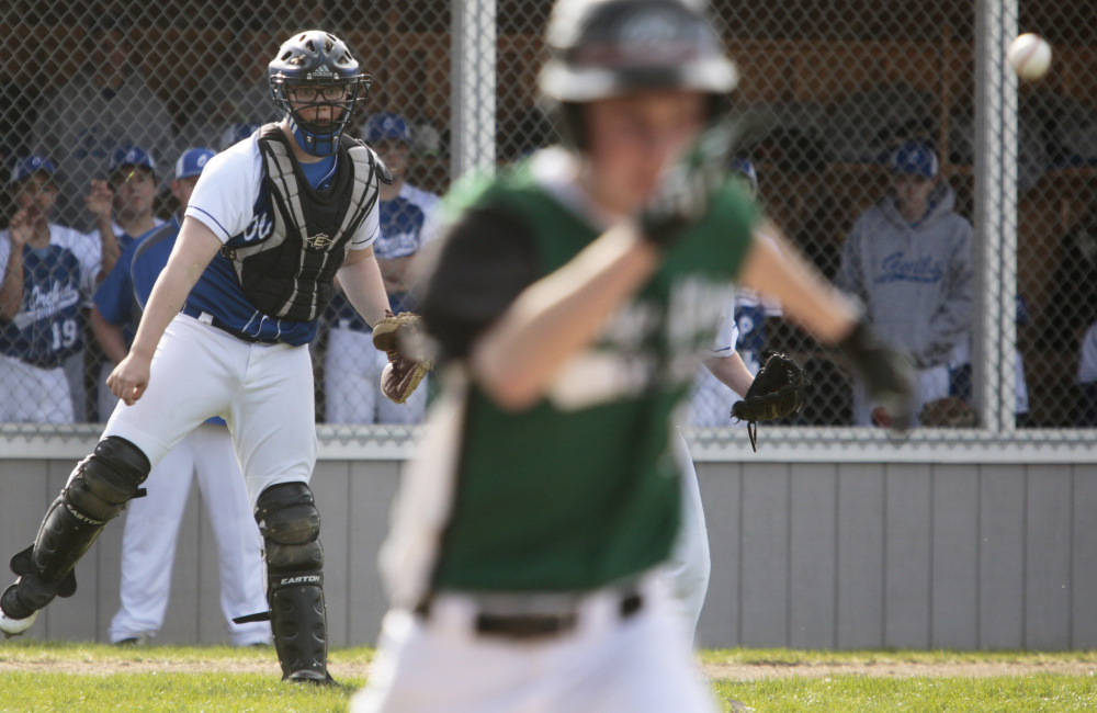 Max Winson of Waynflete heads to first base Monday as Old Orchard Beach catcher Evan O'Donnell watches his throw get there in time. Old Orchard pulled away to a 9-1 victory.