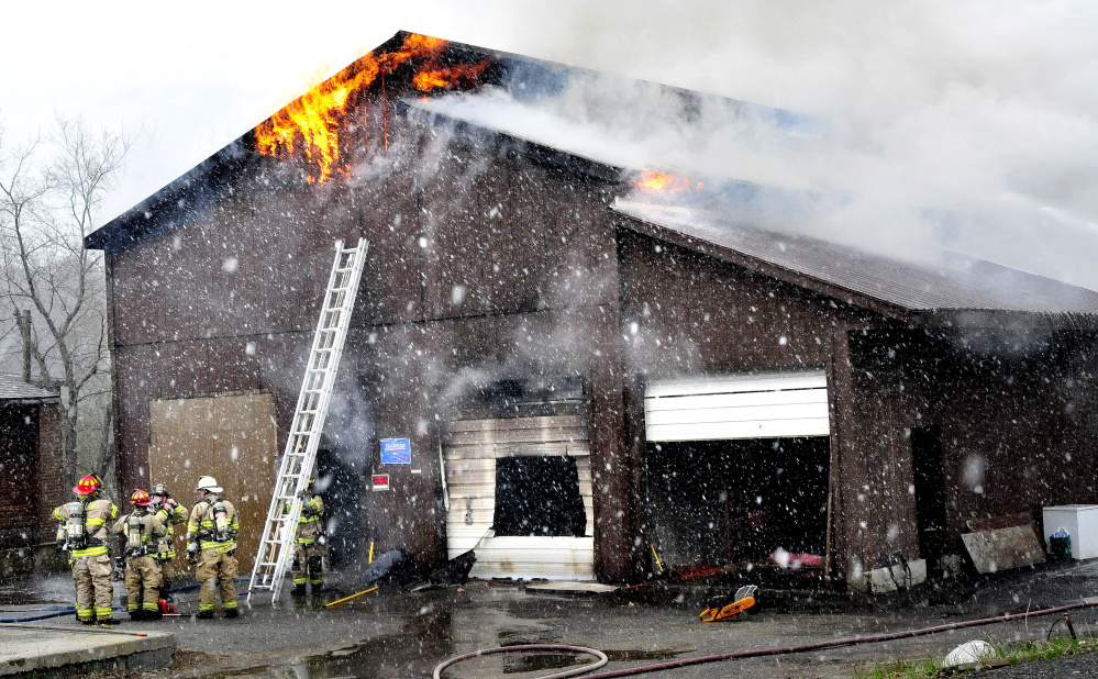 Firefighters set up a ladder to fight the fire that destroyed a large building at the former Dan's Used Cars in Benton on Tuesday.