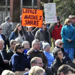 University of Maine in Farmington students Allyson Hammond, left, and Nickolas Bray hold up signs Tuesday criticizing Gov. Paul LePage during the dedication of the Theodora Kalikow Education Center at the school.