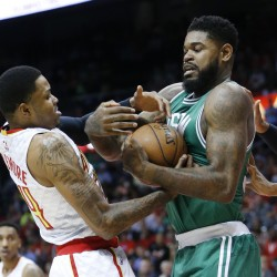 Hawks forward Kent Bazemore and Celtics forward Amir Johnson battle for control of the ball in the first half. (Photos by The Associated Press)