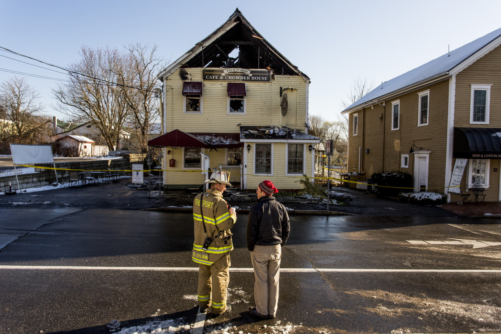 Deputy Fire Chief Eric Sylvain speaks with Hugh Wade of Freeport, a co-owner of the building that housed the Corsican restaurant.