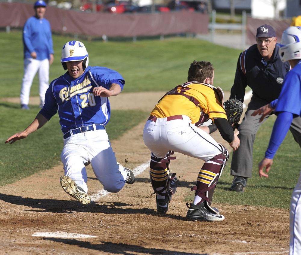 Connor Aube, who scored three runs for Falmouth, slides across the plate in the second inning Wednesday as Cape Elizabeth catcher Brendan Tinsman awaits the throw.