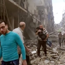 In this image made from video and posted online from Validated UGC, a man carries a child after airstrikes hit Aleppo, Syria, on Thursday.