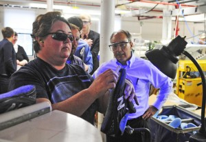 U.S. Rep. Bruce Poliquin, R-2nd District, watches the construction of an athletic shoe during a tour of the New Balance factory in Norridgewock. A change in federal law could require the defense department to buy U.S.-made shoes for service members.