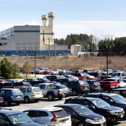 Vehicles sit Thursday in an Idexx employee parking lot just several hundred yards from the Calpine power plant in Westbrook. Calpine said the accidental emissions that coated cars in the lot April 12 occurred during maintenance work done every five to eight years.