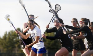 Olivia Stucker of Falmouth draws a crowd of Waynflete defenders during their girls' lacrosse game Thursday. Among the defenders are Lydia Giguere, left; Ali Pope, center; and Clair Dubois, second from right. Falmouth came away with a 17-6 victory.