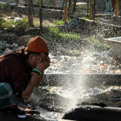 An Indian village man sprinkles water from a broken pipe onto his face in a village in Samba district, some 40 kilometres (25 miles) from Jammu, India, Friday, April 29, 2016. Much of India is reeling under a weekslong heat wave and severe drought conditions that have decimated crops, killed livestock and left at least 330 million Indians without enough water for their daily needs. (AP Photo/Channi Anand)