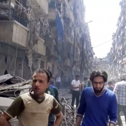 Men look at damaged buildings after airstrikes hit the rebel-held part of the contested city of Aleppo, Syria, on Thursday, killing more than a dozen people.