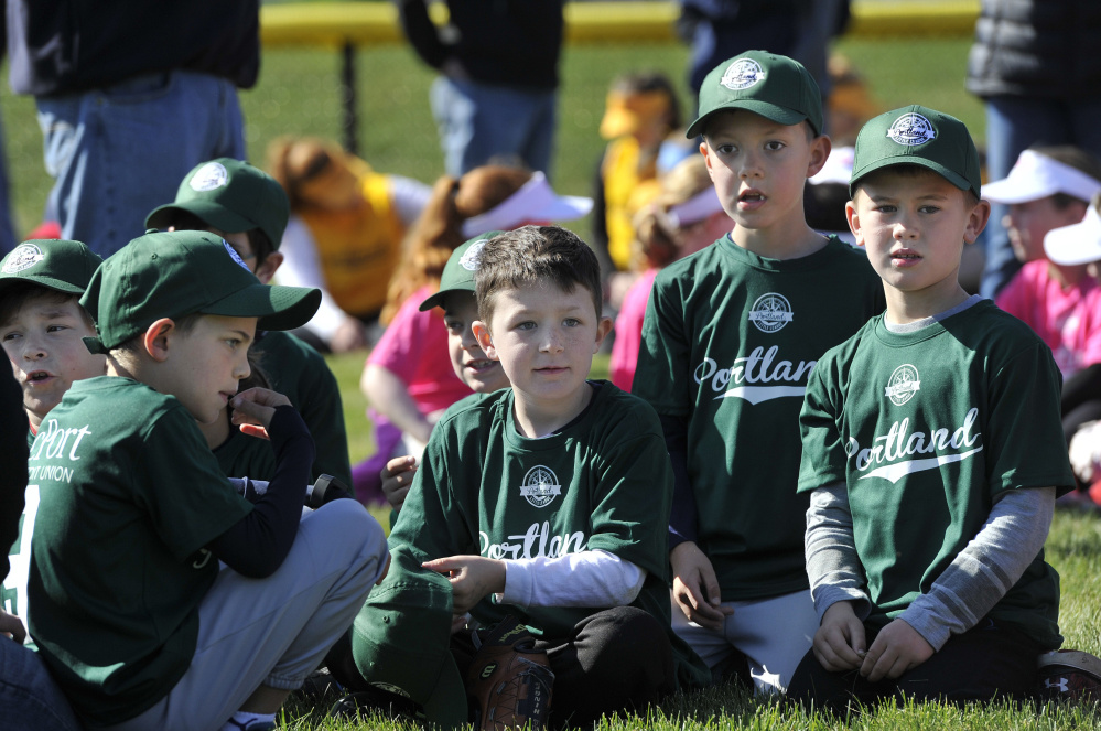 From left, cPort Credit Union Little Leaguers Jack O'Connell, 8, Jaxon Roberts, 7, Rowen Reed, 6, and Quinn Derrig, 7, sit with their team during Little League Opening Day ceremonies Saturday in Portland.