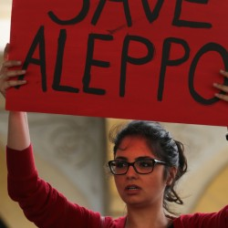 A protester holds up a placard during a protest in downtown Beirut, Lebanon, Saturday, April 30, 2016, against Syrian President Bashar Assad's military operations against areas held by insurgents around the country, mostly in the northern city of Aleppo that has been the main point of violence. (AP Photo/Bilal Hussein)
