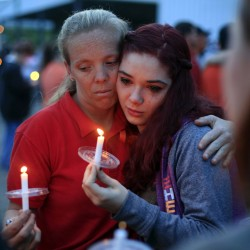 Amber Cassell, 16, right, gets a hug from Margaret Williams as they hold candles during the vigil at the Pike County Fairgrounds in Piketon, Ohio, on Friday.
