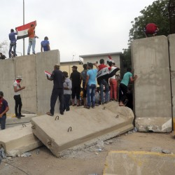 Supporters of Shiite cleric Muqtada al-Sadr walk over the blast walls surrounding Baghdad's highly fortified Green Zone on Saturday. Dozens of protesters stormed the Parliament building, carrying Iraqi flags and chanting against the government.