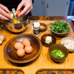 With her ingredients organized on a cutting board, Christine Burns Rudalevige breaks an egg while making a spicy Jonah crab and local greens omelette.