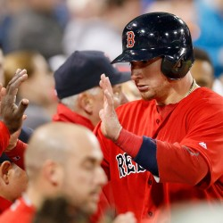 Boston Red Sox's Christian Vazquez is congratulated at the dugout after scoring on an RBI single by Dustin Pedroia during the sixth inning of a baseball game against the Toronto Blue Jays at Fenway Park, Friday, April 15, 2016, in Boston.  (AP Photo/Mary Schwalm)