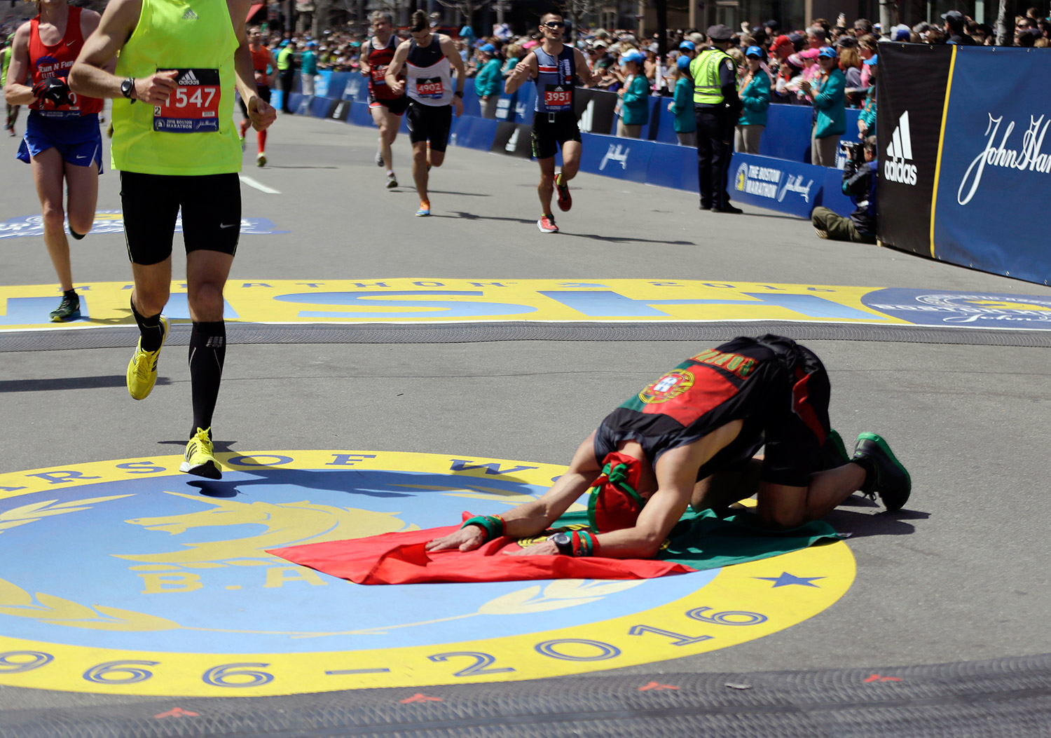 Of canada kneels on a flag of portugal after finishing the marathon