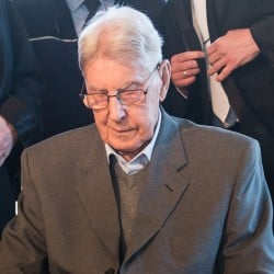 94-year-old former SS sergeant Reinhold Hanning, front, sits in the courtroom in Detmold, Germany, Friday, April 29, 2016. Henning plans to make his first statement to the German court since his trial opened in February on 170,000 counts of accessory to murder over allegations he served as a guard at the Nazis' Auschwitz death camp. Standing behind him are his lawyers Andreas Scharmer, left, and Johannes Salmen, right. (Bernd Thissen/Pool Photo via AP)